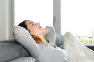 Happy relaxed woman resting on a couch at home with arms in the head